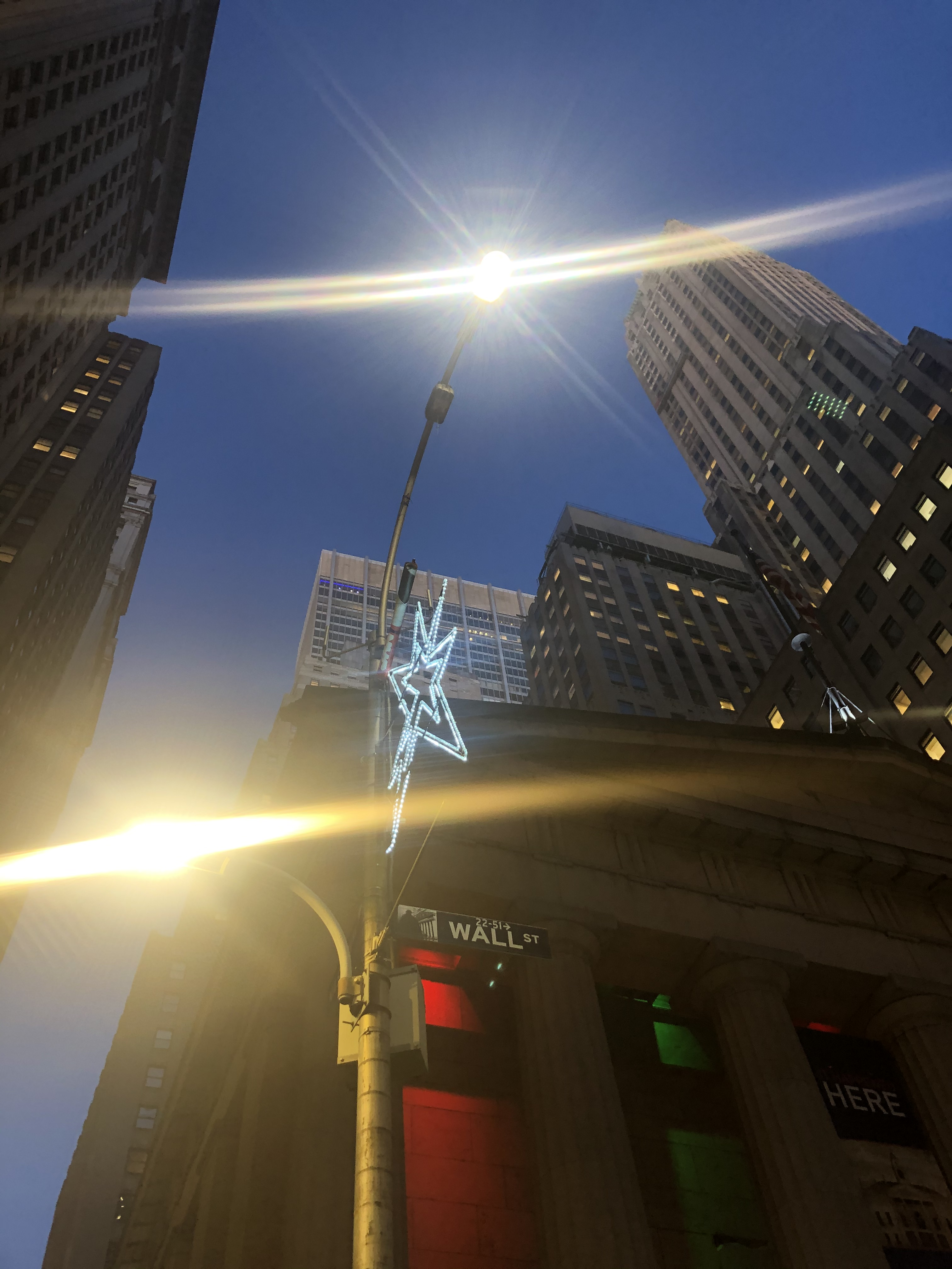 Star-shaped Christmas lights attached to a light pole near a Wall Street street sign